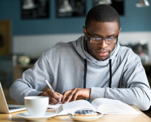 Focused millennial african american student in glasses making notes writing down information from book in cafe preparing for test or exam, young serious black man studying or working in coffee house, wondering the best season to go back to school.