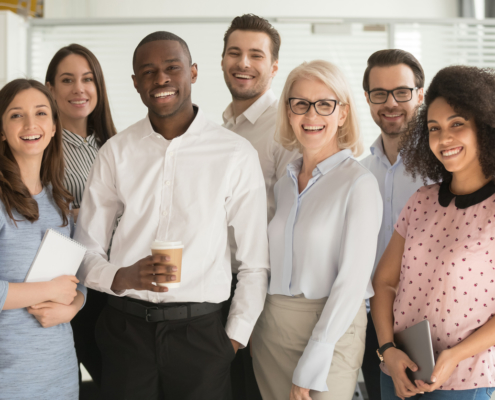 Positive multi racial corporate team posing looking at camera, their boss thinking about Ways to Ensure Your Employees' Happiness.