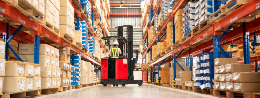 Worker in forklift-truck loading packed goods in huge distribution warehouse with high shelves., wondering How the Logistics Industry is Impacted by the COVID-19 Pandemic.